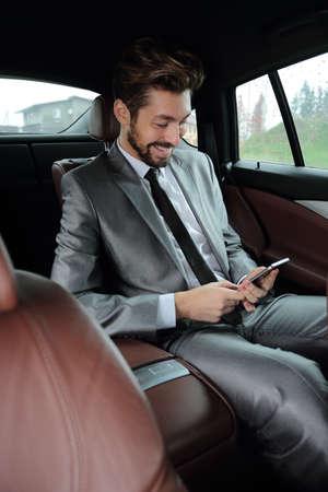 34f05ef5bb #66957737 - Handsone exitoso hombre de negocios usando el teléfono móvil en  el asiento trasero del coche