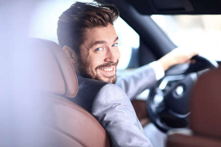 successful man: Portrait of a handsome successful business man driving his car Stock Photo