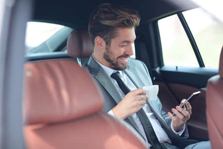 back seat: Handsone successful businessman using mobile phone in back seat of car
