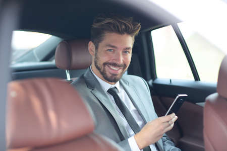 Handsone successful businessman using mobile phone in back seat of car