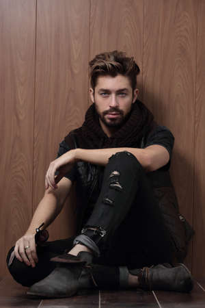 casual fashion: Handsome fashionable man posing against a background of a wooden wall.