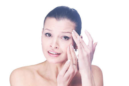 appear: Young girl examining her face and wrinkles that can appear isola