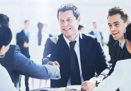 negocios internacionales: Empresario maduro estrechar la mano para sellar un acuerdo con su socio y colegas en una oficina moderna