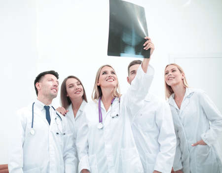 physiotherapists: Smiling doctors are analyzind the x-ray. Medical office interior