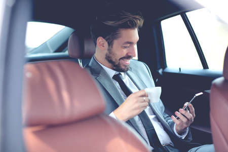 Happy young businessman using mobile phone in back seat of car Stock Photo