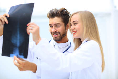 medical and radiology concept - two doctors looking at x-ray