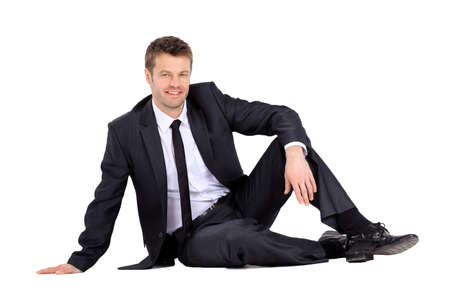 Smiling businessman sitting on the floor Stock Photo