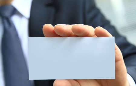 unrecognizable: Mans hand showing business card - closeup shot on grey background