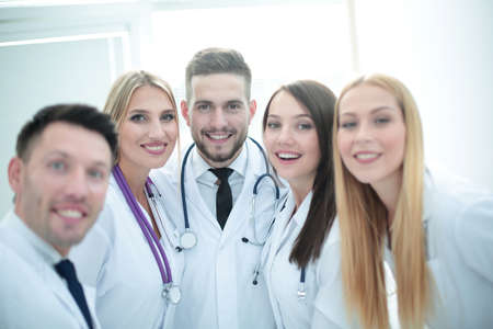Smiling team of doctors at hospital making selfie.