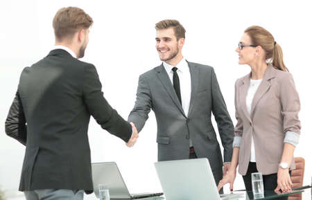 deal in: Happy smiling business people shaking hands after a deal in offi