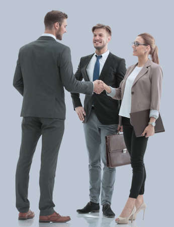 Image of business partners making handshake isolated on gray.