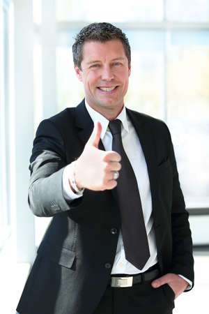 swanky: Portrait of a business man with crossed arms showing thumb up Stock Photo
