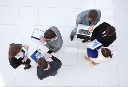 로비에 서있는 재무 문서와 비즈니스 팀