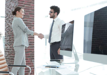professionally: handshake of business partners on background of blank screens