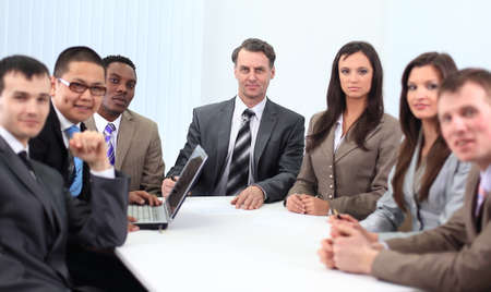 Businessmen and businesswomen  sitting at a desk as a team. photo