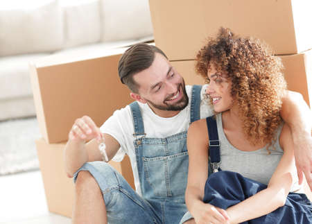 moving box: smiling couple on the background of large cardboard boxes.