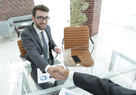 professionally: handshake business partners at your Desk