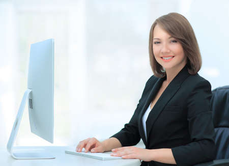 Happy businesswoman typing on computer at her desk Stock Photo