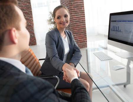 handdruk met collega's achter een bureau
