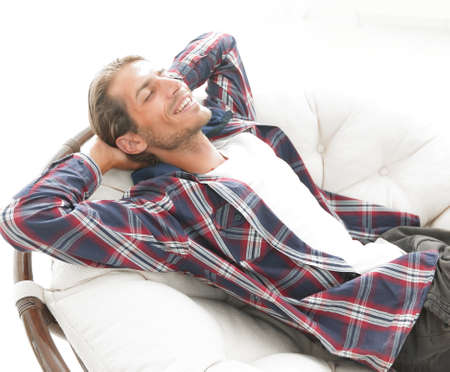 contemporary living room: modern guy is resting sitting in a large comfortable chair. side view.