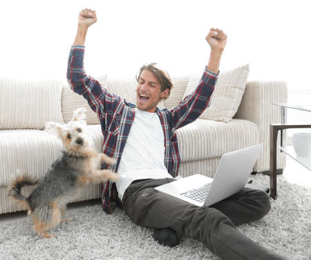 family sofa: happy young man exults with his dog sitting in the living room
