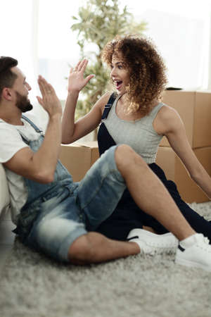 moving box: concept of a house, people and real estate - a happy couple barking each other five with a new house