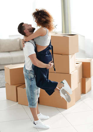 young couple hugging each other in new apartment.