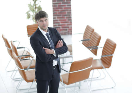 company: Business man standing in an empty meeting room Stock Photo