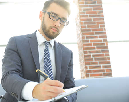 Businessman writing in a notebook in an office Stock Photo