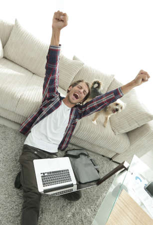 cute guy: happy guy with laptop jubilant in spacious living room.
