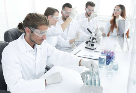 Scientists working with a microscope and make notes in the workplace Stock Photo