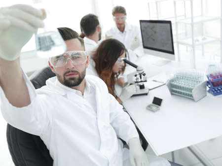 biochemist with flask Petri sitting at a Desk Stock Photo