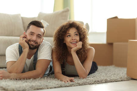 Young couple lying on the rug on the background of a new apartment Stock Photo