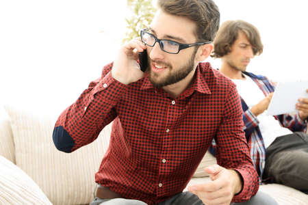 house call: guy talking on smartphone sitting on sofa. Stock Photo
