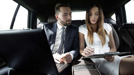man and woman discussing work documents in taxi Stockfoto