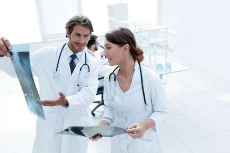 Male surgeon with nurse examining x-ray report Stock Photo