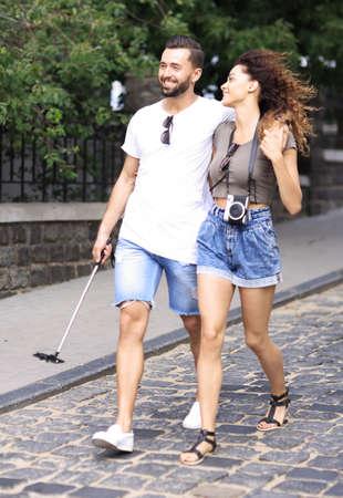 Cheerful young couple walking on urban street Stock Photo