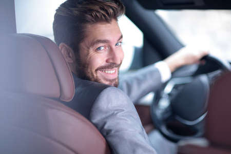 Successful man sitting behind the wheel of a prestigious car