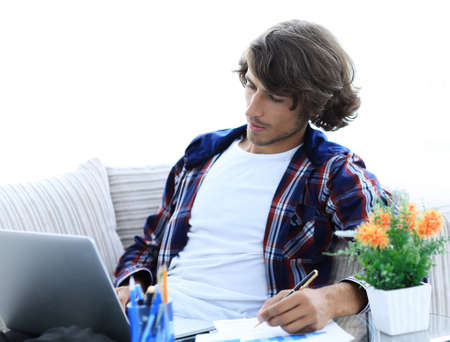 confident guy working with laptop at home.