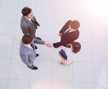 concept of partnership: investor and businessman shaking hands a