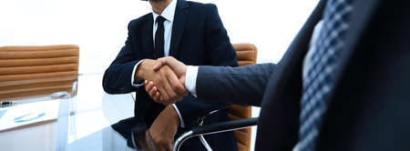 bottom view. confident handshake of business partners sitting at a Desk Stock Photo