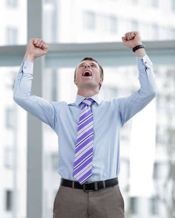 Businessman celebrating with his fists raised in the air Stock Photo