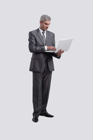 businessman standing with an open laptop