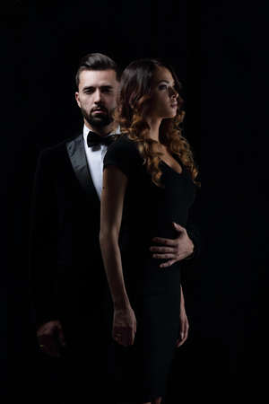 photo of young family couple on black background. Archivio Fotografico