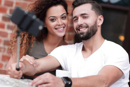 Happy cheerful couple sitting down at a cafe and making selfie Stock Photo