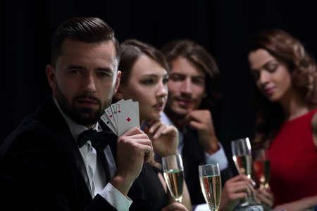 Pokerspieler zu vier Assen über dunklem Hintergrund Standard-Bild - 90785361