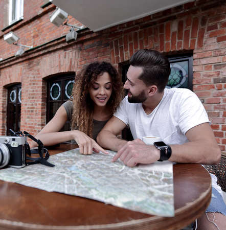Couple in an outdoor cafe using map and planning itinerary Foto de archivo