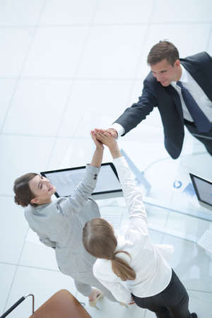 view from the top.members of the business team giving each other a high five above the Desk.
