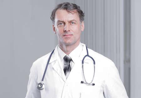 pewnie dorosły lekarz patrząc w kamerę. Zdjęcie Seryjne