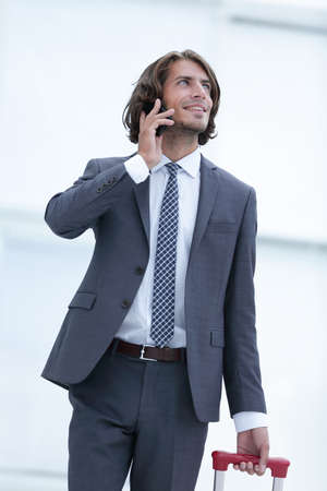businessman with travel suitcase talking on the phone